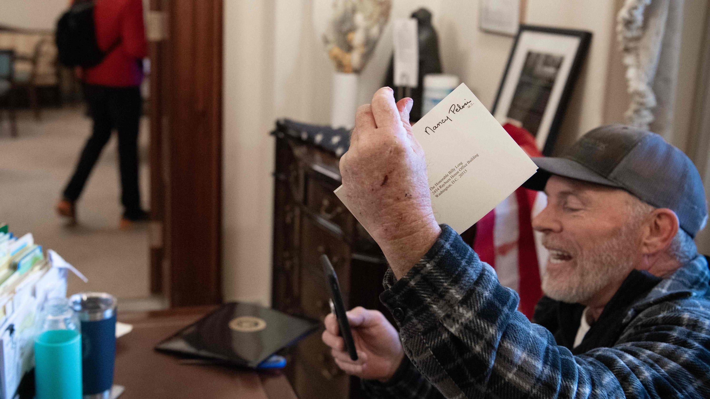 Man in Pelosi desk photo, others