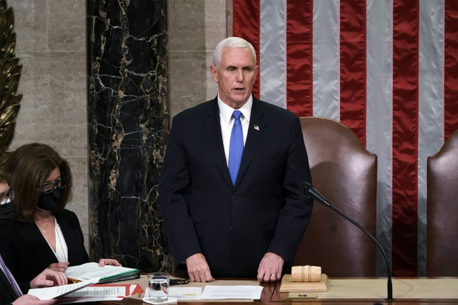 Vice President Mike Pence listens after reading the final certification of Electoral College votes cast in November's presidential election during a joint session of Congress after working through the night, at the Capitol in Washington, Jan. 7. Violent protesters loyal to President Donald Trump stormed the Capitol the day before, disrupting the process.