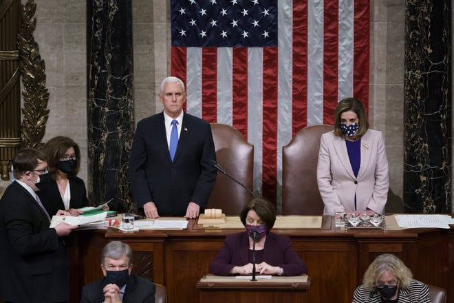 Vice President Mike Pence and Speaker of the House Nancy Pelosi, D-Calif., read the final certification of Electoral College votes cast in November's presidential election during a joint session of Congress after working through the night at the Capitol in Washington on Jan. 7. Violent protesters loyal to President Donald Trump stormed the Capitol, disrupting the process.
