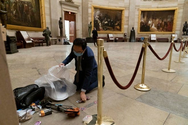 Rep. Andy Kim, D-N.J., cleans up debris and personal belongings strewn across the floor of the Rotunda in the early morning hours of Jan. 7, 2021, after protesters stormed the Capitol in Washington, on Wednesday.