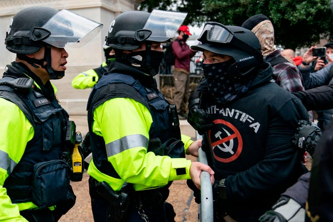 A protester, who claims to be a member of the Proud Boys, confronts police officers as supporters of President Donald Trump protest outside the U.S. Capitol on Jan. 6, 2021, in Washington, D.C.