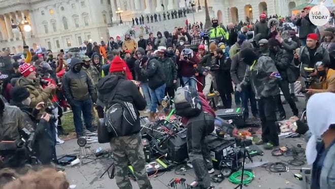 A pro-Trump mob piling up and smashing media equipment in front of the Capitol.