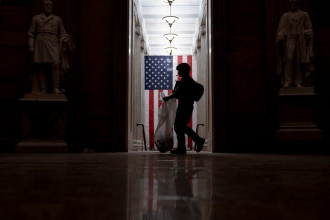 An ATF police officer cleans up debris and personal belongings strewn across the floor of the Rotunda in the early morning hours of Thursday, Jan. 7, after protesters stormed the Capitol in Washington, on Wednesday. (AP Photo/Andrew Harnik)
