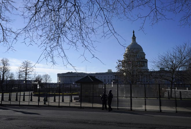 Authorities stand by newly placed fencing around the U.S. Capitol grounds on Thursday, the day after rioters stormed the U.S. Congress in Washington. [AP PHOTO/EVAN VUCCI]