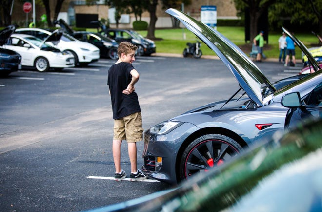 Coleman Lyons looks in the hood of his father's Tesla Model S P100D at the Electric Vehicle Car Show and Expo in Austin in 2019. [ELI IMADALI/AMERICAN-STATESMAN]