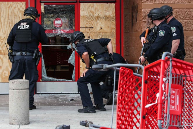 Austin police on May 31 check the damaged door of the Target store at Capital Plaza in East Austin after a break-in during a rally decrying police brutality.