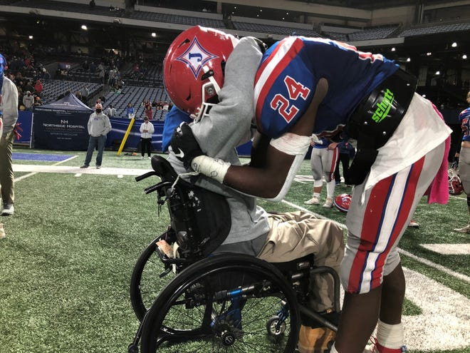 Jefferson QB Malaki Starks (24) is embraced by Jefferson assistant coach Devon Gales after the Dragons fell in the Class 4A state final in Atlanta. (Photo/Ryne Dennis, Athens Banner-Herald)