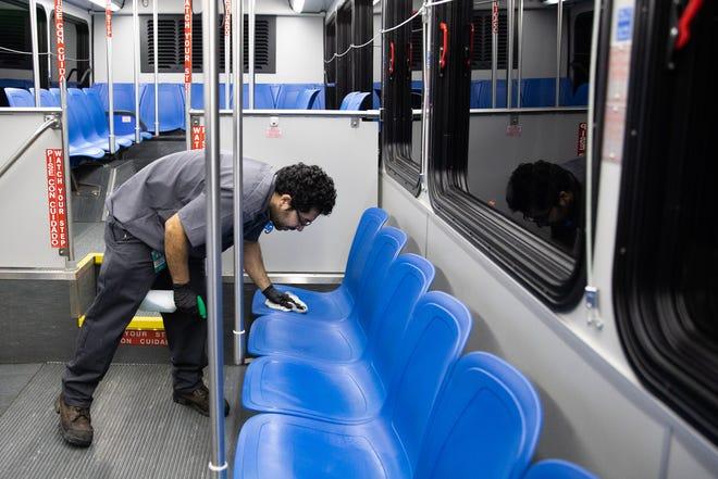 Jonathan Vasquez, an Athens Transit employee, cleans and sanitizes a bus last March. (Photo/Gabriella Audi, www.gabriellamariephoto.com)