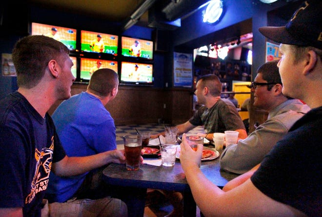 KSU students Ryan Seuffrett (left), Eddie Walaszewski, Dustin Evans, Ryan Ziemke and Justin Cady at the Water Street Tavern watching Kent State baseball pitcher Tyler Skulina throw against the Oregon Ducks in the NCAA Super Regionals on Monday, May 11, 2012 in Kent, Ohio. (Paul Tople/Akron Beacon Journal)