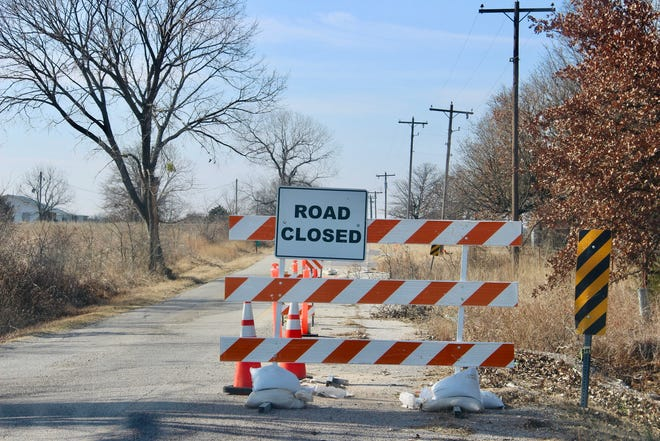 A barricade blocks the right side of Stobtown Road, where construction has been halted due to a civil lawsuit.