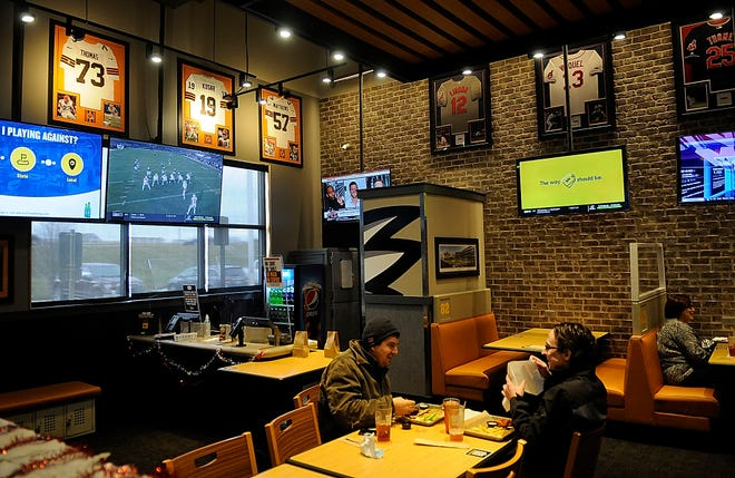Replica jerseys of Cleveland Browns greats Joe Thomas, Bernie Kosar and Clay Matthews hang on a wall at Buffalo Wild Wings in Ashland. The restaurant will only be decorating for the Ohio State game this weekend, because both Cleveland and Pittsburgh fans stop in to watch the games. TOM E. PUSKAR/TIMES-GAZETTE.COM