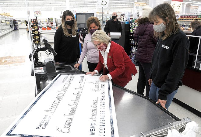 Miller's Hawkins Market's store manager Karen Graves, center, signs the ceremonial check from the store's Hunger Games promotion as Associated Charities Miranda Brown and Chris Box along with Milller's Hawkins Market's Jodi Liggett watch on Friday.
