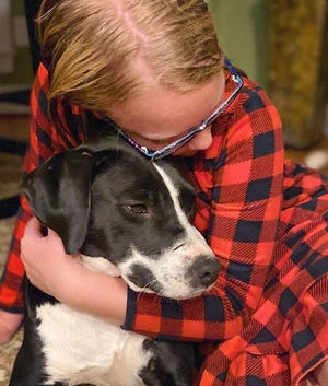 Ella Anderson hugs Mulligan, a dog she bonded with while volunteering at the Aiken County Animal Shelter.