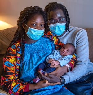 Neinlah Kollie, left, of Morrisville, holds newborn son, Haqeem, with his dad, Abdoulaye Apithy, by her side Thursday.