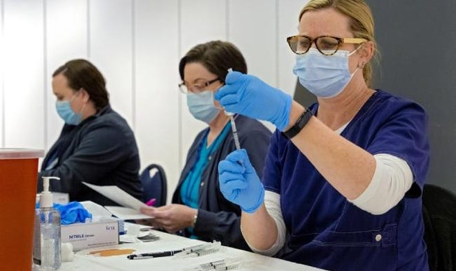 A nurse fills syringes with the COVID-19 vaccine for distribution in the Cleveland County Health Department's vaccine pod at Sooner Fashion Mall in Norman on Thursday, Jan. 7.