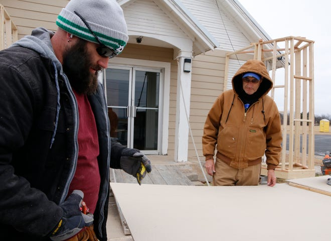 Kreig Maxwell (foreground) and his dad, Freedom Fellowship pastor Jim Maxwell, work on a cold Friday morning as they make upgrades to the Early church's children's ministry building, pictured behind them.