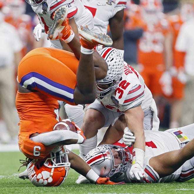 Ohio State linebacker Tuf Borland (32), here helping tea-kettle Clemson's Travis Etienne in the Sugar Bowl, is among the players in Monday's national title game who plans to participate in the Senior Bowl.