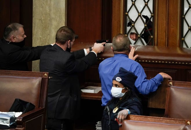 Police with guns drawn watch as protesters try to break into the House Chamber at the U.S. Capitol.