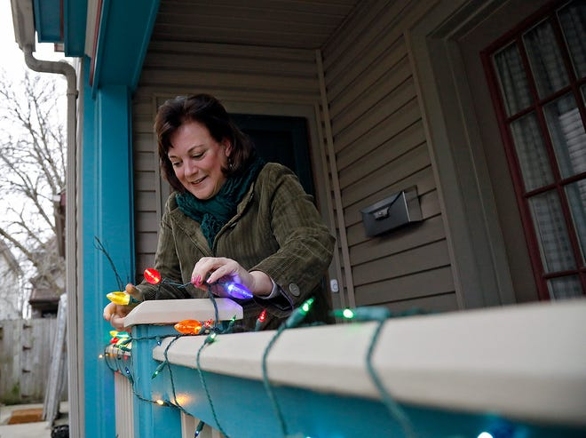 Lisa Ohmer adds a string of lights around her railing at her Merion Village home. Ohmer encouraged her neighbors to leave their Christmas lights up through the spring as a show of community and optimism during a difficult time.