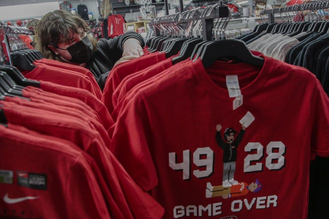 Amy Flanagan, of Grove City, looks through Ohio State merchandise Friday at College Traditions on Lane Avenue. A Buckeyes' win in the national championship game would be a big boost for retailers whose sales have suffered mightily during this most unusual football season.