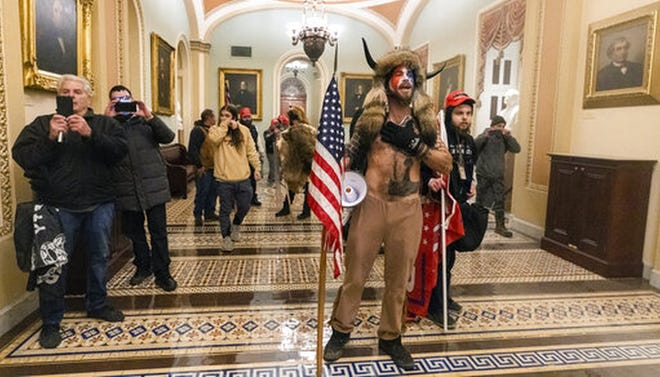 A protester outside the U.S. Senate chambers Wednesday, garbed in a distinctive horned headdress, was falsely identified by some Trump supporters as an Antifa infiltrator.