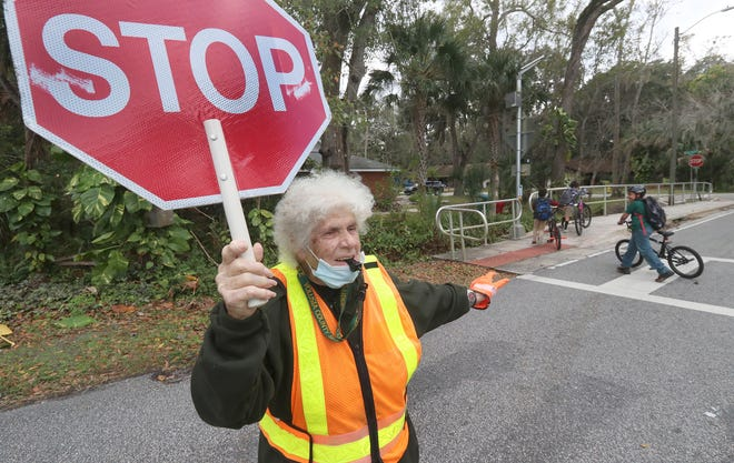 Retiring Volusia school crossing guard Anna Snyder, 90, stops traffic for students on their way home from Sugar Mill Elementary School, Friday January 8, 2021 for the last time.