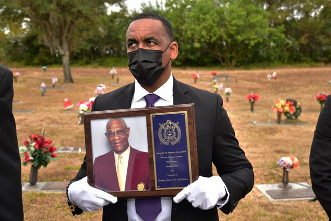 Jermaine Mckinney of the Omega Psi Phi fraternity, holds a picture of Coach Cy McLairen on Friday, Jan. 8, 2021, at the graveside service for the B-CU athletics icon, who died Dec. 28 at age 89.