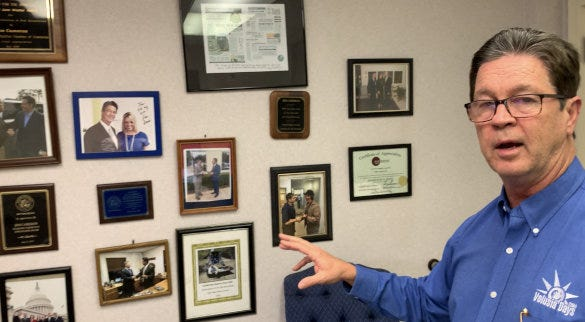 Jim Cameron, senior vice president of government relations for the Daytona Regional Chamber of Commerce, points to a wall of photos of him with some of the many elected officials he has worked with the past 38 years, on Dec. 21, 2020. He recently announced his decision to leave his job as a lobbyist for the chamber at the end of April 2021.
