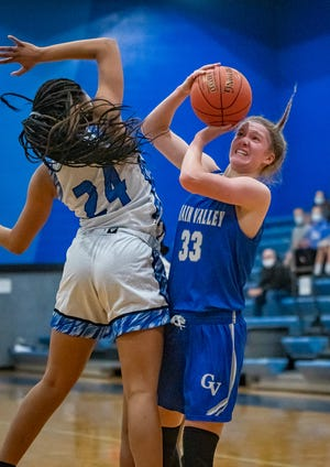 Grain Valley sophomore guard Grace Slaughter, right, goes up for a contested shot against Raytown defender Amani Henry (24) in Thursday's conference game at Raytown. Slaughter poured in a school-record 45 points but it wasn't enough as the host Blue Jays claimed a 74-56 win.