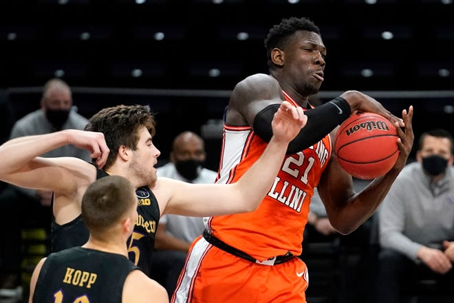 Illinois center, Kofi Cockburn, right, rebounds the ball against Northwestern center Ryan Young during the second half of Thursday night's game in Evanston.