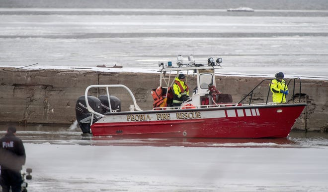 A Peoria Fire and Rescue boat prepares to come ashore Friday at National Marine Sales off Galena Road after searching all morning for a kayaker reported missing Thursday night. Sarah Gray, 45, was wearing a yellow life vest and piloting an 11-foot pink kayak.