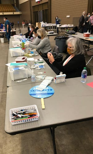 A group of nurses at the Lubbock Memorial Civic Center get the Moderna vaccine ready for doses.