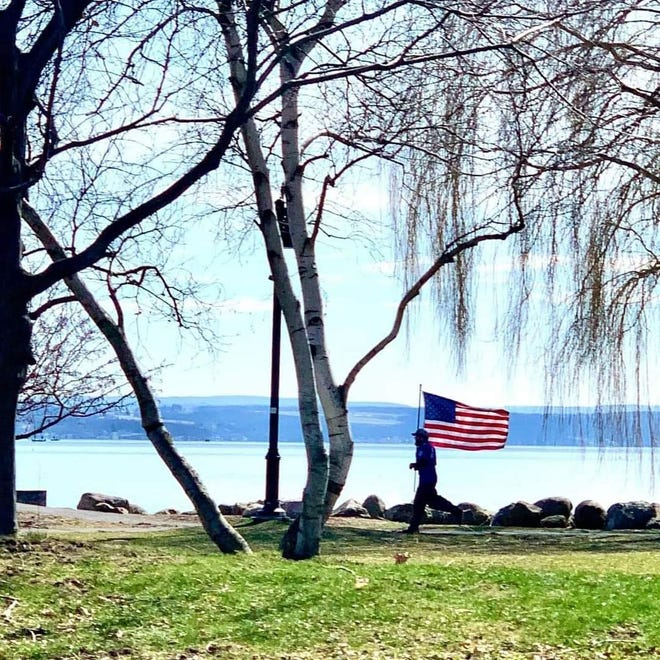 """Marine veteran Eric Morehouse, shown running with the American flag along Canandaigua Lake to honor fellow Marines, hopes people who see him """"go out and Google this person or say a prayer for this person's friend or family."""""""