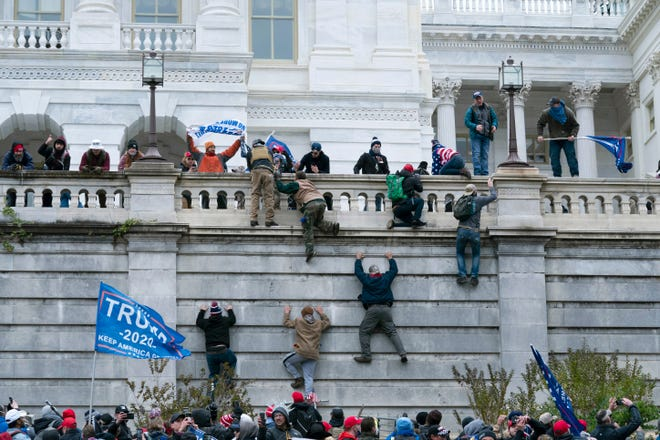 Supporters of President Donald Trump climb the west wall of the the U.S. Capitol on Wednesday, Jan. 6, 2021, in Washington. [AP Photo/Jose Luis Magana]