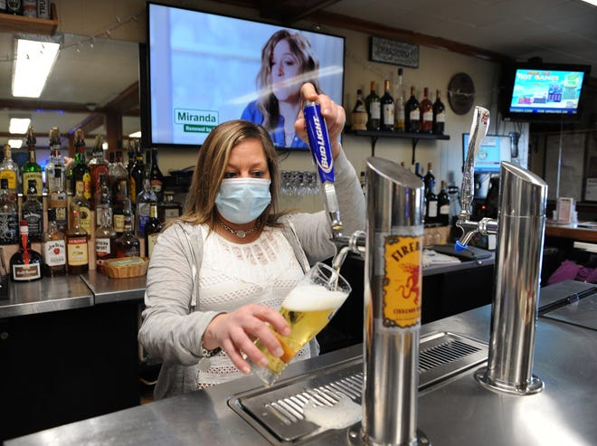 At the Framingham Columbus Club, bartender Myla Vallee pours a beer, Jan. 8, 2021.