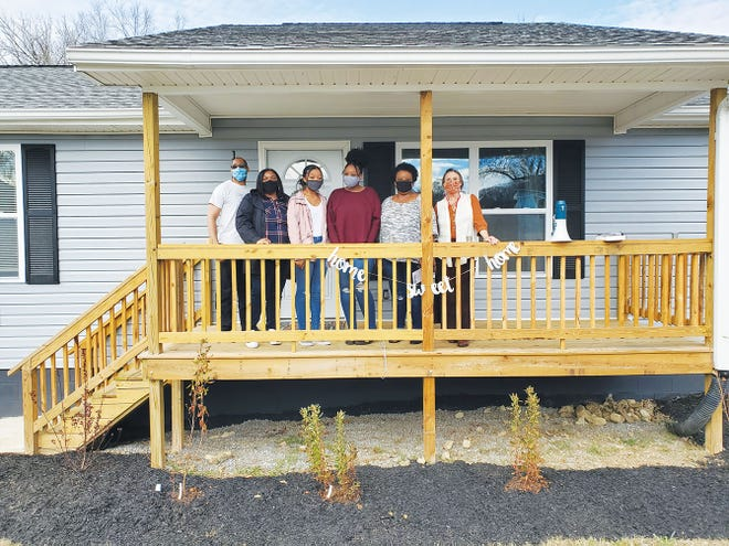 The Rev. Derrick Hammond, Rebecca Soles' family, and Clinch River Habitat for Humanity Executive Director Charlotte Bowers Cunningham stand on the porch of Soles' new home.