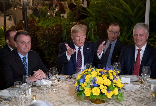 Brazilian President Jair Bolsonaro, left, is shown having dinner with President Donald Trump at Mar-a-Lago on March 7. Bolsonaro's press secretary tested positive for the coronavirus days after participating in meetings that weekend at the club.