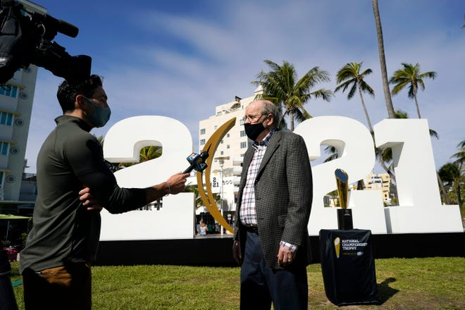 Bill Hancock, executive director of the College Football Playoff, wears a mask while being interviewed during a news conference Thursday in Miami Beach.