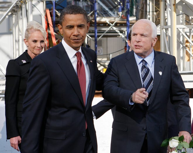 Former Republican presidential candidate, Sen. John McCain, R-Ariz., and Democratic presidential  candidate, Sen., Barack Obama, D-Ill., talk as they walk together after participating in a Ground Zero 9/11 memorial observance in 2008 in New York. McCain's wife Cindy, left, looks on.