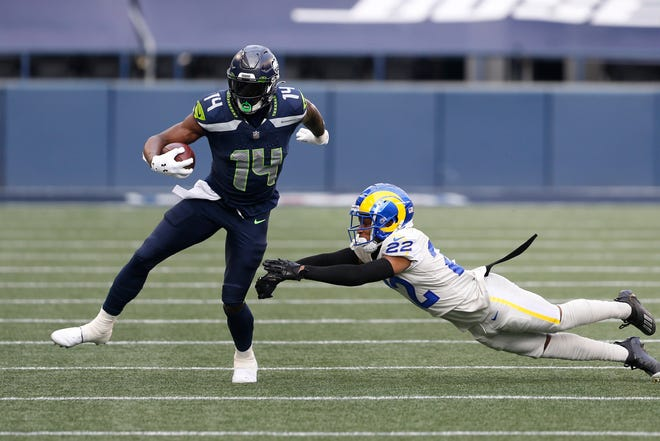 Seattle wide receiver DK Metcalf (14) evades Los Angeles Rams cornerback Troy Hill during their Dec. 27 game in Seattle.