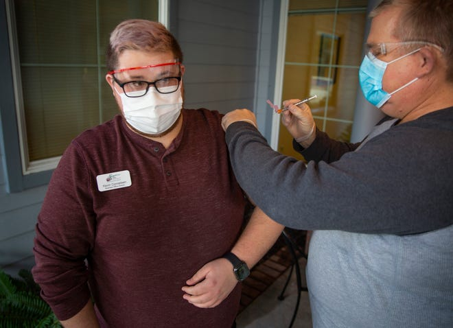 Kevin Conradsen, left, business office director at Sweetbriar Villa Assisted and Memory Care in Springfield, receives the virus vaccine Friday from from nurse Mike Sherwood.