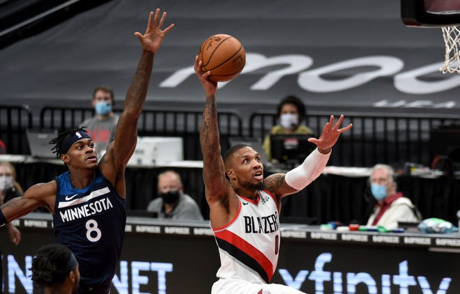 Portland's Damian Lillard, right, drives to the basket past Minnesota's Jarred Vanderbilt during the second half of the Trail Blazers' 135-117 win on Thursday in Portland.