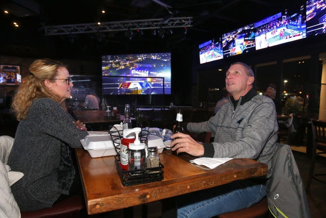 Carrie and Mike Lackey enjoy time at Jerzee's All American Sports Grille in Jackson Township on Thursday. Sports bars like Jerzee's are frustrated that they won't be able to stay open past 10 p.m. on Sunday or Monday for the Cleveland Browns playoff game and the Ohio State college football national title game. Gov. Mike DeWine says he will not extend the curfew.