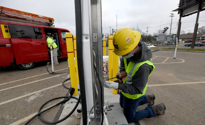 Workers with Hilscher-Clarke Electric Company, including Jack Lewis,  install Greenlots electric vehicle charging stations for the city of Canton in the parking lot of Stadium Park.