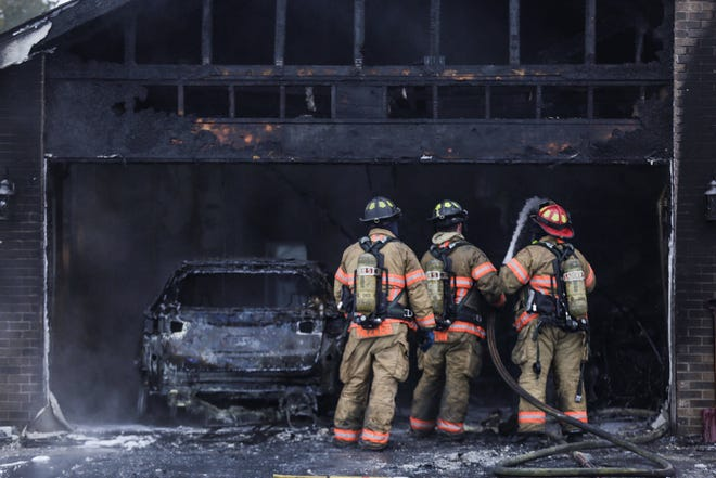 Firefighters work on overhaul after a house fire Friday, Jan. 8, 2021, at the 6600 block of North Point Road left a vehicle charred inside a garage at the duplex in Rockford.