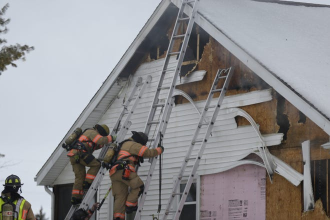 Rockford firefighters climb ladders Friday, Jan. 8, 2021, while working to bring a house fire at 6600 North Point Road under control.