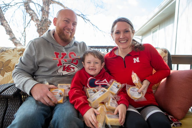 Stacy and Quint Cook, owners of Stumpy's Smoked Cheese, sit with their son Kipton, 5, Friday with a pile of their smoked cheeses on their back patio. The business owners started Stumpy's in 2017 and have seen a boom in business since then.