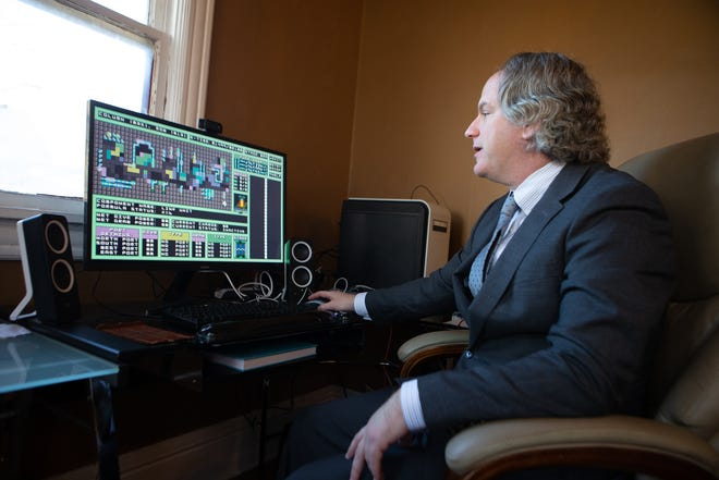 """Tyler Jaggers shows off his newest video game, """"Kontrol Flow,"""" from his home office in Topeka on Dec. 17. Jaggers, who runs his company Overidon Omnimedia out of his home office, moved to Topeka in October with help from the Choose Topeka program."""