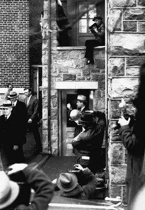 Photographers surround aviator Charles A. Lindbergh, without hat, as he leaves the courthouse in Flemington, N.J., Jan. 9, 1935 during the trial of Bruno Hauptmann on charges of kidnapping and murdering the Lindbergh baby boy.