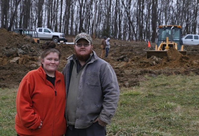 Jessica and Glenn Clarke stand near the area where their new home will be built. (TimesReporter.com / Jim Cummings)